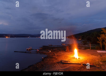 Summer ends with a 'Ring of Fire' on Labor Day weekend, bonfires lit along the shores of Great Sacandaga Lake, southern Adirondacks, New York State. - Stock Photo