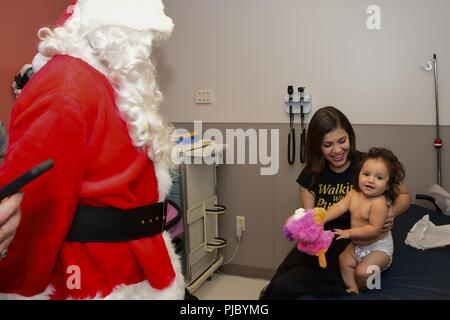 – Santa Claus gives Sophia a toy during Rolling Thunder's Christmas in July. These motorcycle club members visit NMCP twice a year, visiting children in the Pediatrics Ward, Pediatric Intensive Care Unit and Emergency Room. Santa Claus hands out presents to each child receiving medical care. - Stock Photo