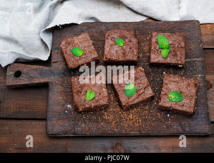 baked square pieces of brownie brownie pie on an old brown wooden cutting board, top view - Stock Photo