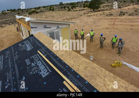 """U.S. Airmen from the 169th Civil Engineer Squadron, construct homes for Native American veterans during the """"Deployment for Training"""" mission to Gallup, New Mexico, July 12, 2018. Airmen assigned to the South Carolina Air National Guard's 169th Fighter Wing partnered with the Southwest Indian Foundation to provide all phases of the construction process including carpentry, framing, electrical, plumbing and site work. - Stock Photo"""