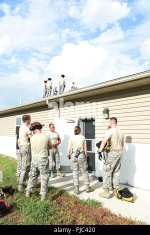 Members from the 155th Air Refueling Wing Fire Department train on several requirements of Fire Fighting Safety at the Nebraska Air National Guard Base War Skills Building July 13, 2018, Lincoln, Nebraska.   The members participated in hands-on dynamic entry, ladder safety, and discussed various structural concerns to refresh their fire-fighting skills. - Stock Photo