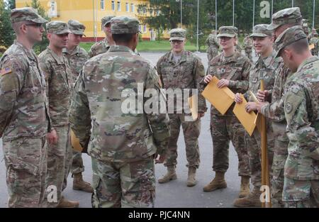 Yavoriv, Ukraine - Class 703-2018 Basic Leadership Course instructed by 7th Army Training Command non-commissioned officers completed a graduation ceremony at the Yavoriv Combat Training Center (CTC) July 11. Squad members join together to share stories and show appreciation for their instructor as he gives them final words of wisdom and guidance on being junior leaders of todays military. - Stock Photo