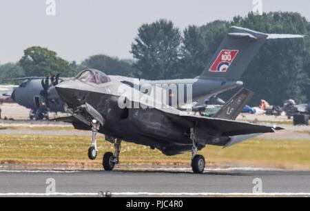 A U.S. Air Force lands F-35A Lightning II during the 2018 Royal International Air Tattoo at RAF Fairford on July 13, 2018. This year's RIAT celebrated the 100th anniversary of the RAF and highlighted the United States' ever-strong alliance with the UK. - Stock Photo