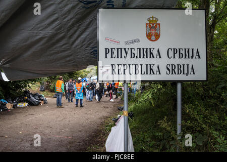 BERKASOVO, SERBIA - SEPTEMBER 27, 2015: Refugees gathering behing the border sign on Serbia Croatia boundary in Berkasovo Bapska, on the Balkans Route - Stock Photo