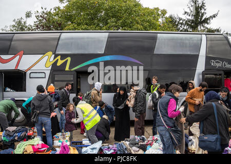 BERKASOVO, SERBIA - SEPTEMBER 27, 2015: Muslim refugees, mainly women, looking at clothes donations outside of a bus at the border between Serbia and  - Stock Photo