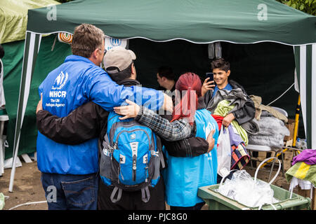 BERKASOVO, SERBIA - SEPTEMBER 27, 2015: Workers of the UNHCR, the United Nations Agency for refugees, taking pictures with a migrant at the border bet - Stock Photo
