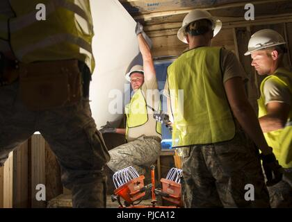 U.S. Air Force Staff Sgt. Donald Johnson, an electrician from the 133rd Civil Engineer Squadron, helps hang a sheet of drywall within a transportable modular home in Gallup, N.M., July 23, 2018. The homes are being constructed for Navajo Veterans as part of joint Innovative Readiness Training program led by the Naval Mobile Construction Battalion 22 in partnership with the Southwest Indian Foundation. - Stock Photo