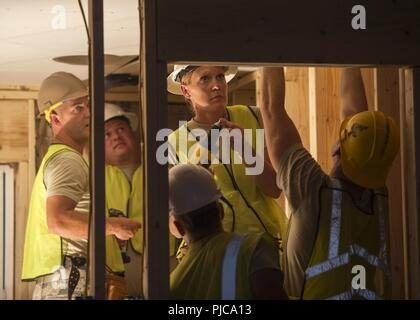 U.S. Air Force Chief Master Sgt. Sarah Miller, Operations Chief from the 133rd Civil Engineer Squadron, secures a sheet of drywall to the ceiling of a transportable modular home in Gallup, N.M., July 23, 2018. The homes are being constructed for Navajo Veterans as part of joint Innovative Readiness Training program led by the Naval Mobile Construction Battalion 22 in partnership with the Southwest Indian Foundation. - Stock Photo