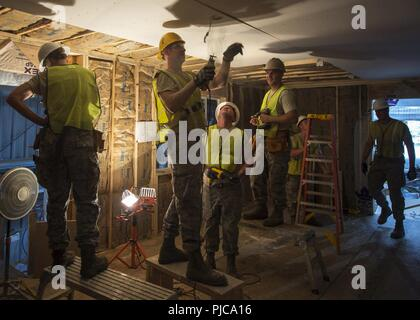 U.S. Air Force Airmen from the 133rd Civil Engineer Squadron hang and cut sheets of drywall on a transportable modular home in Gallup, N.M., July 23, 2018. The homes are being built for Navajo Veterans as part of joint Innovative Readiness Training program led by the Naval Mobile Construction Battalion 22 in partnership with the Southwest Indian Foundation. - Stock Photo