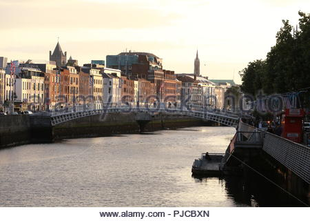 The Ha'penny Bridge over the River Liffey in Dublin Ireland as the sun sets on a beautiful summer's day. - Stock Photo