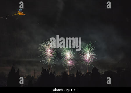 White and green fireworks on the feast of the patron saint of the city whose church is visible in the background, Vittorio Veneto, Italy - Stock Photo