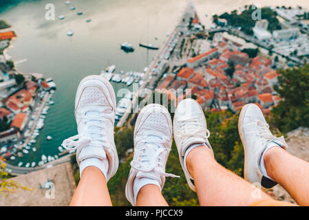 couple legs at hill with beautiful view of kotor city on background. summer vacation - Stock Photo
