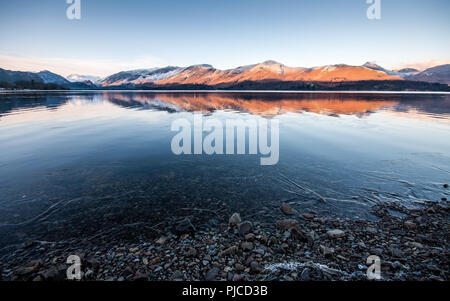 Winter snow lies on Catbells mountain, reflected in Derwent Water lake, in England's Lake District. - Stock Photo