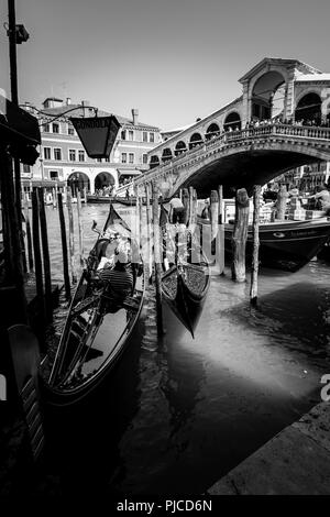 Two gondolas getting ready for a ride on the Grand Canal in Venice, while tourists watching the scene from the Rialto Bridge in the background - Stock Photo