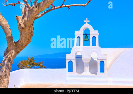 Old white belfry and dry tree in Oia town in Santorini, Greece - Greek landscape - Stock Photo