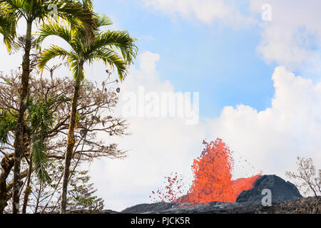 lava from Kilauea Volcano erupts from a fissure on Pohoiki Road, just outside of Leilani Estates subdivision, and next to the Puna Geothermal Ventures - Stock Photo