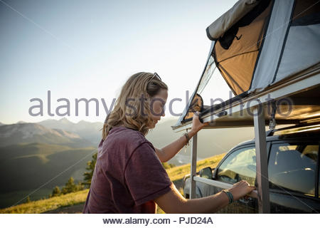 Woman camping, climbing up to SUV rooftop tent in idyllic mountain field, Alberta, Canada - Stock Photo