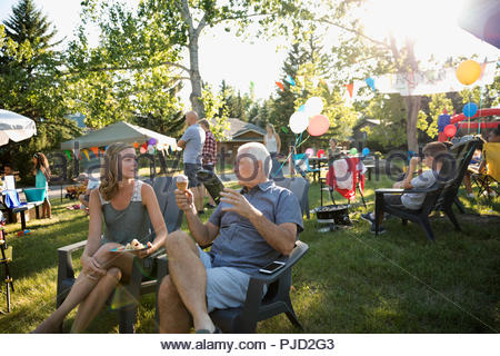 Senior father and daughter eating ice cream cone and talking at summer neighborhood block party in park - Stock Photo