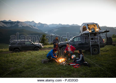 Friends camping, enjoying campfire on remote mountain hilltop, Alberta, Canada - Stock Photo