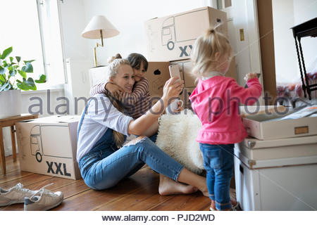 Mother and daughter taking selfie, taking a break from moving - Stock Photo