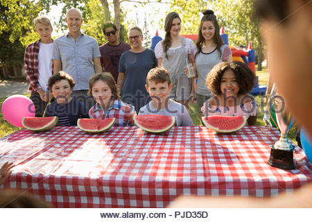 Kids preparing for watermelon eating contest at summer neighborhood block party in park - Stock Photo