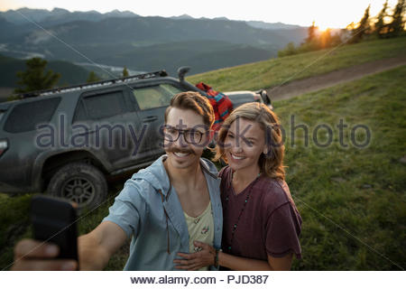 Happy couple taking selfie with camera phone in front of SUV on mountain road, Alberta, Canada - Stock Photo
