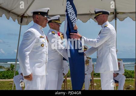 ASAN BEACH, Guam (July 19, 2018) As Command Master Chief Joe Arnold looks on, Capt. Jeffrey Kilian (left) passes the regimental flag to Capt. Steven Stasick during 30th Naval Construction Regiment's (30 NCR) change of command ceremony at the War in the Pacific National Historical Park Asan Beach Unit. The passing of colors from an outgoing commanding officer to an incoming one ensures the unit and its Sailors are never without leadership. Stack relived Kilian during the ceremony. - Stock Photo