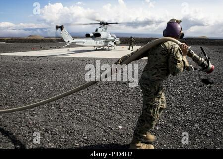 POHAKULOA TRAINING AREA, Hawaii (July 18, 2018) U.S. Marine Corps Cpl. Garrett Subik, a bulk fuel specialist with Marine Wing Support Detachment 24, moves a fuel line towards a landing pad in order to start fueling a AH-1W Super Cobra helicopter during a field test for an Expeditionary Mobile Fuel Additization Capability system as part of Rim of the Pacific (RIMPAC) exercise at Pohakuloa Training Area, Hawaii, July 18, 2018. RIMPAC provides high-value training for task-organized, highly capable Marine Air-Ground Task Force and enhances the critical crisis response capability of U.S. Marines in - Stock Photo