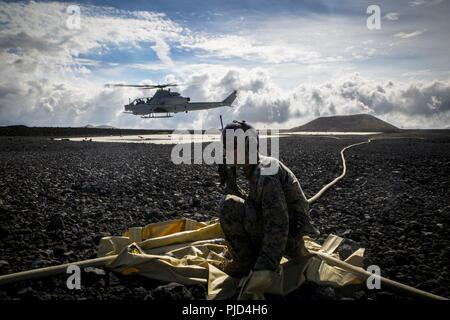 POHAKULOA TRAINING AREA, Hawaii (July 18, 2018) U.S. Marine Cpl. Michael Michehl, a line noncommissioned officer with Marine Wing Support Detachment 24, controls forward arming and refueling point operations after refueling a Bell AH-1W Super Cobra during a field test for the Expeditionary Mobile Fuel Additization Capability system as part of Rim of the Pacific (RIMPAC) exercise at Pohakuloa Training Area, Hawaii, July 18, 2018. RIMPAC provides high-value training for task-organized, highly capable Marine Air-Ground Task Force and enhances the critical crisis response capability of U.S. Marine - Stock Photo
