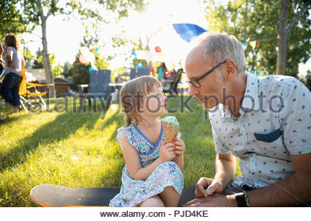 Father and daughter with ice cream cone at summer neighborhood block party in park - Stock Photo