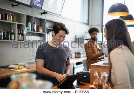 Cafe cashier using digital tablet at counter - Stock Photo