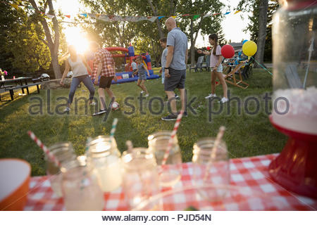Neighbors playing soccer at summer neighborhood block party in sunny park - Stock Photo