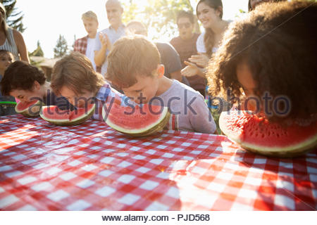 Kids enjoying watermelon eating contest at summer neighborhood block party in park - Stock Photo