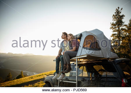 Serene couple relaxing at SUV rooftop tent in idyllic mountain field, Alberta, Canada - Stock Photo