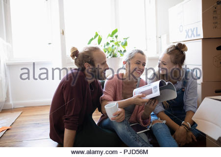 Friends reading book, taking a break from moving - Stock Photo
