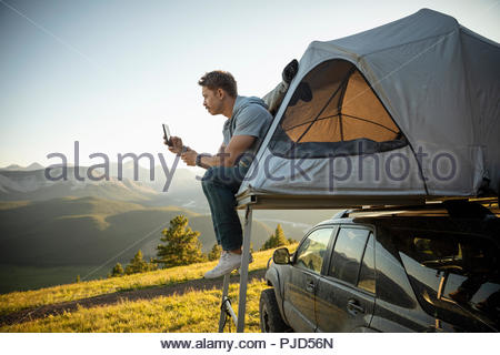 Serene man camping, relaxing at SUV rooftop tent in sunny, idyllic field, Alberta, Canada - Stock Photo