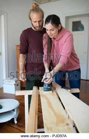 Couple using sander, doing DIY carpentry project - Stock Photo