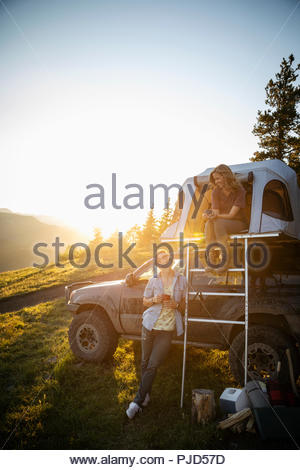 Couple camping, relaxing at SUV rooftop tent in sunny, idyllic field, Alberta, Canada - Stock Photo