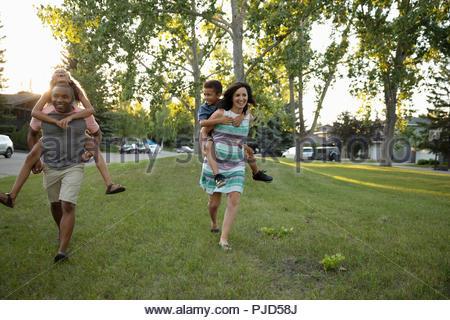 Playful parents piggybacking kids in park - Stock Photo