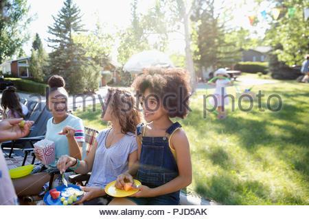 Neighbors eating at summer neighborhood block party in sunny park - Stock Photo