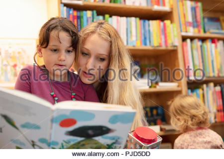 Mother and daughter reading book in bookstore - Stock Photo