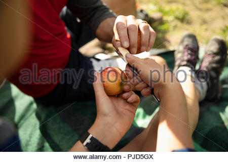 Close up couple cutting and eating fresh apple - Stock Photo