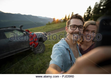 Happy couple taking selfie with camera phone in front of SUV on mountain road - Stock Photo