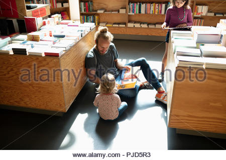 Father reading book to baby daughter on floor in bookstore - Stock Photo