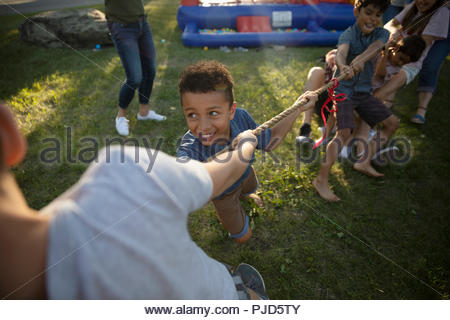 Kids playing tug-of-war in park - Stock Photo
