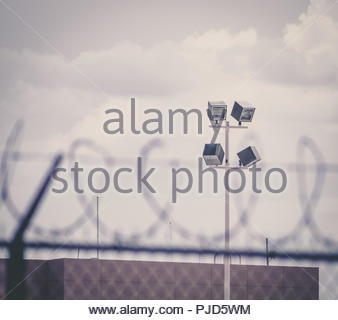 barbed wire and chainlink fence in front of prison lights and brown brick building moody gloom - Stock Photo