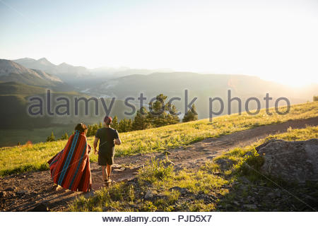Couple wrapped in blanket walking on sunny mountain hilltop, Alberta, Canada - Stock Photo