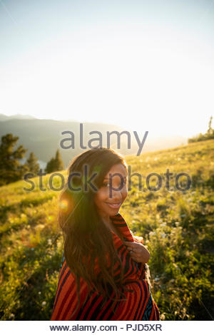 Portrait smiling young woman wrapped in blanket on sunny, idyllic hillside - Stock Photo