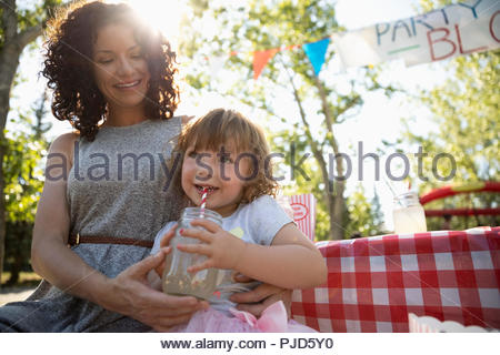 Mother and daughter drinking lemonade at summer neighborhood block party - Stock Photo