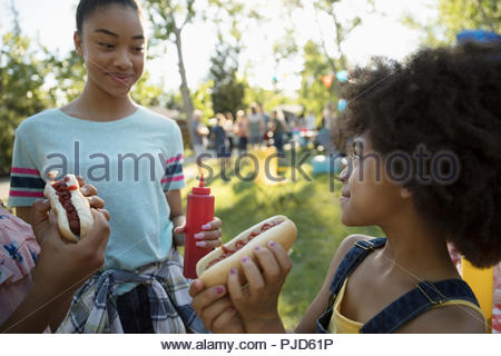 Sisters eating hot dogs at summer neighborhood block party in park - Stock Photo